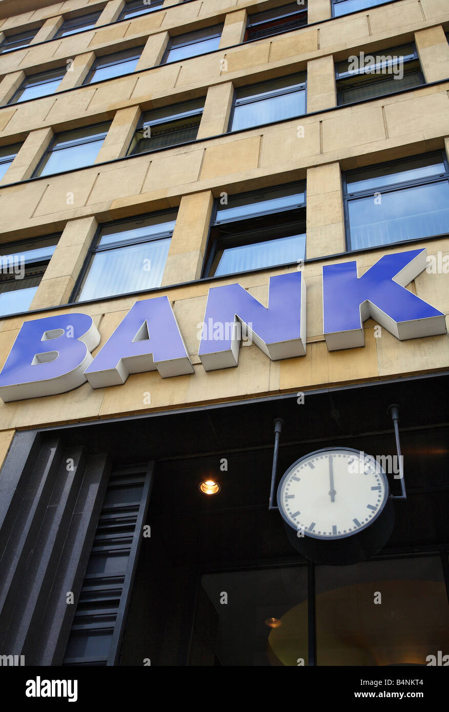BANK sign on a building and a clock showing twelve o'clock - Stock Image
