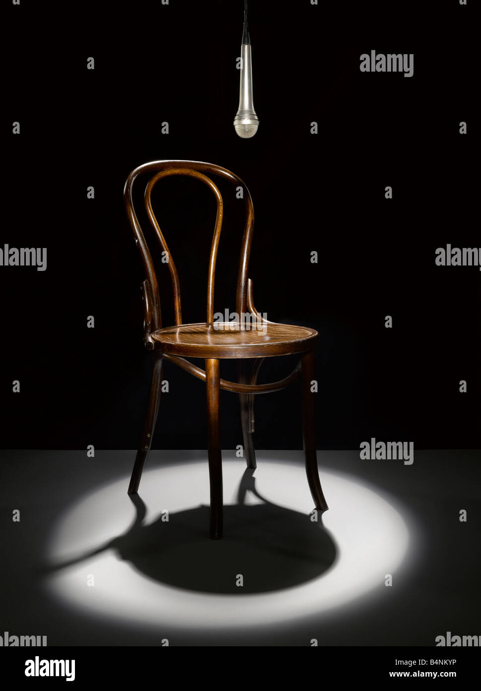 A wooden chair and microphone in the spotlight - Stock Image