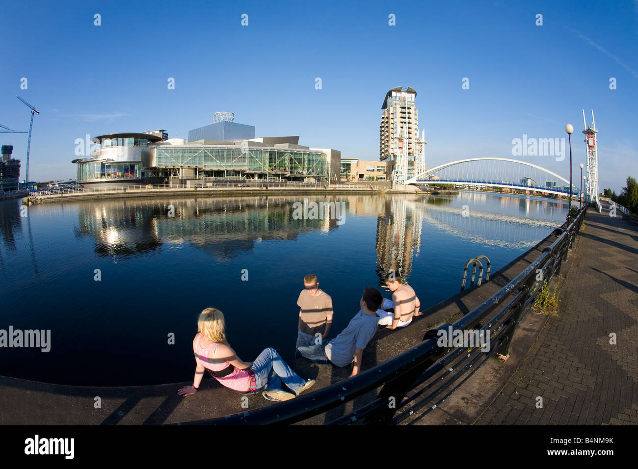 Four young teenagers near Millennium Bridge over the Manchester Ship Canal and Lowry Art Centre Salford Quays Manchester - Stock Image