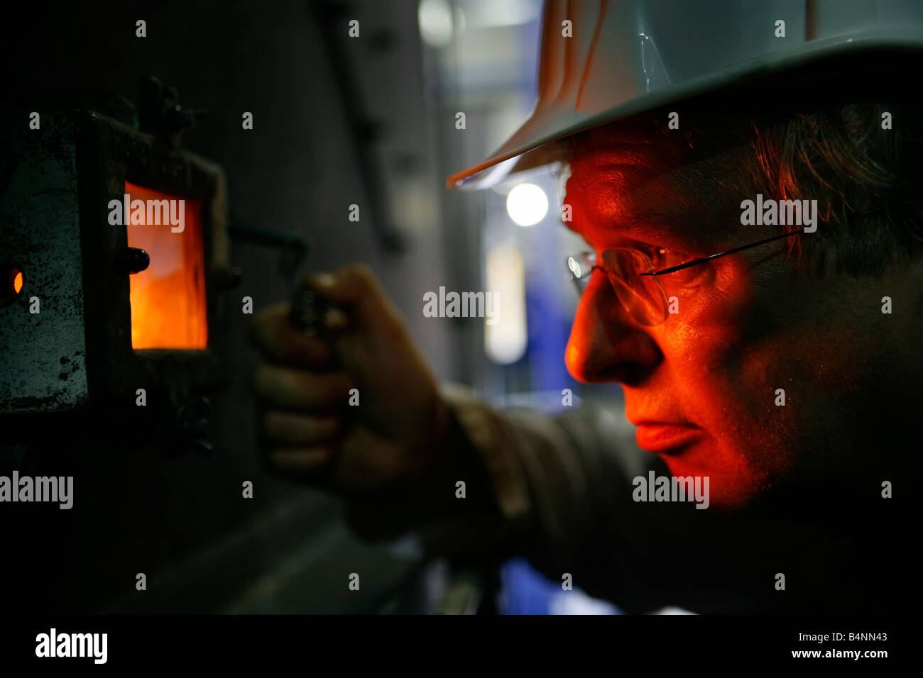 Furnace burning wood chippings to generate electricity Man inspecting furnace through viewing window - Stock Image