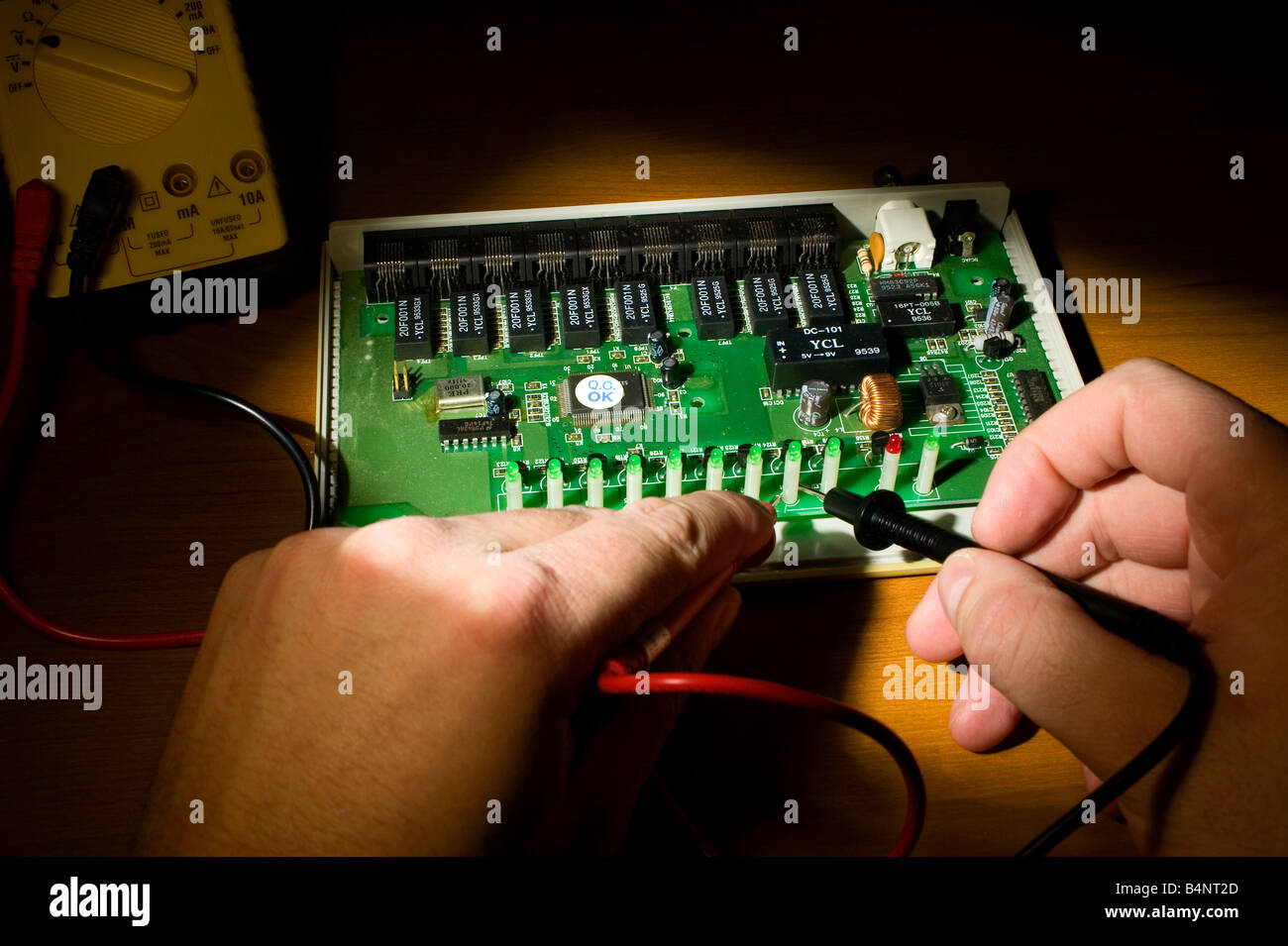 A Circuit Board Is Being Tested With Multimeter And Only The Hands Electronics Test For Series Including Voltmeter Of Tester Are Shown