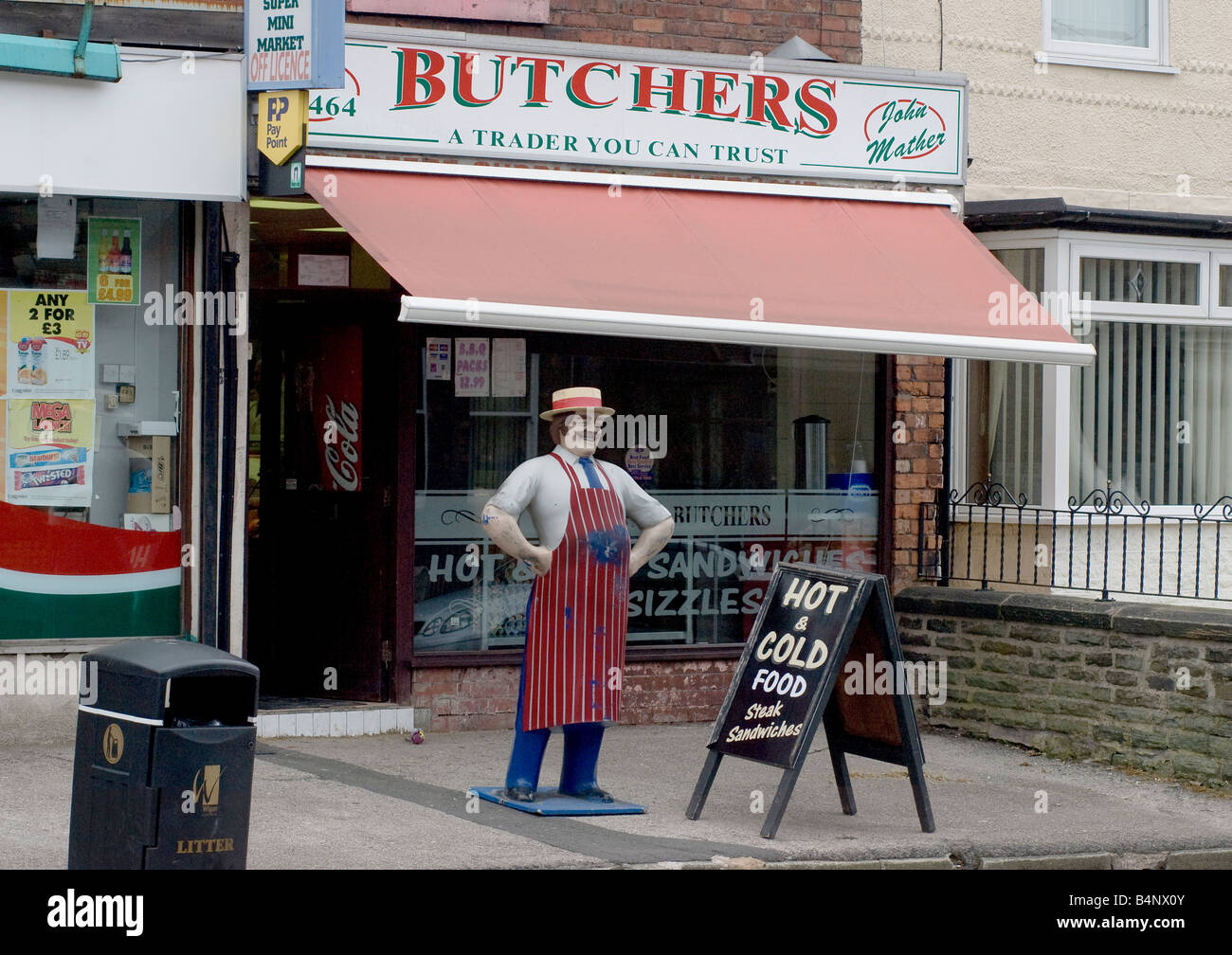 The shopfront of a Butcher's shop with a statue of a butcher in England. - Stock Image