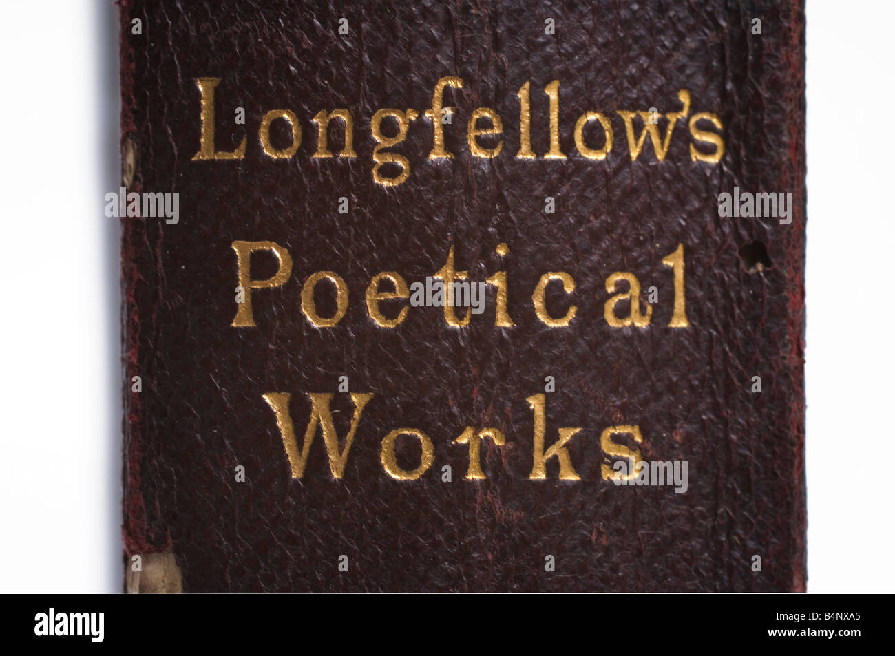 The name of the author Longfellow engraved in gold on the leather binding of an old book of his works - Stock Image