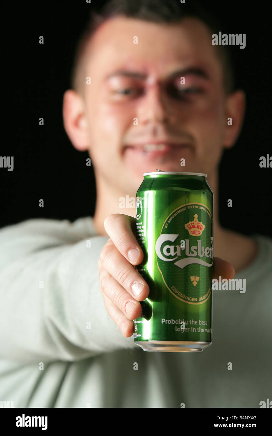 Male model with a black eye holding a can of Carlsberg larger - Stock Image