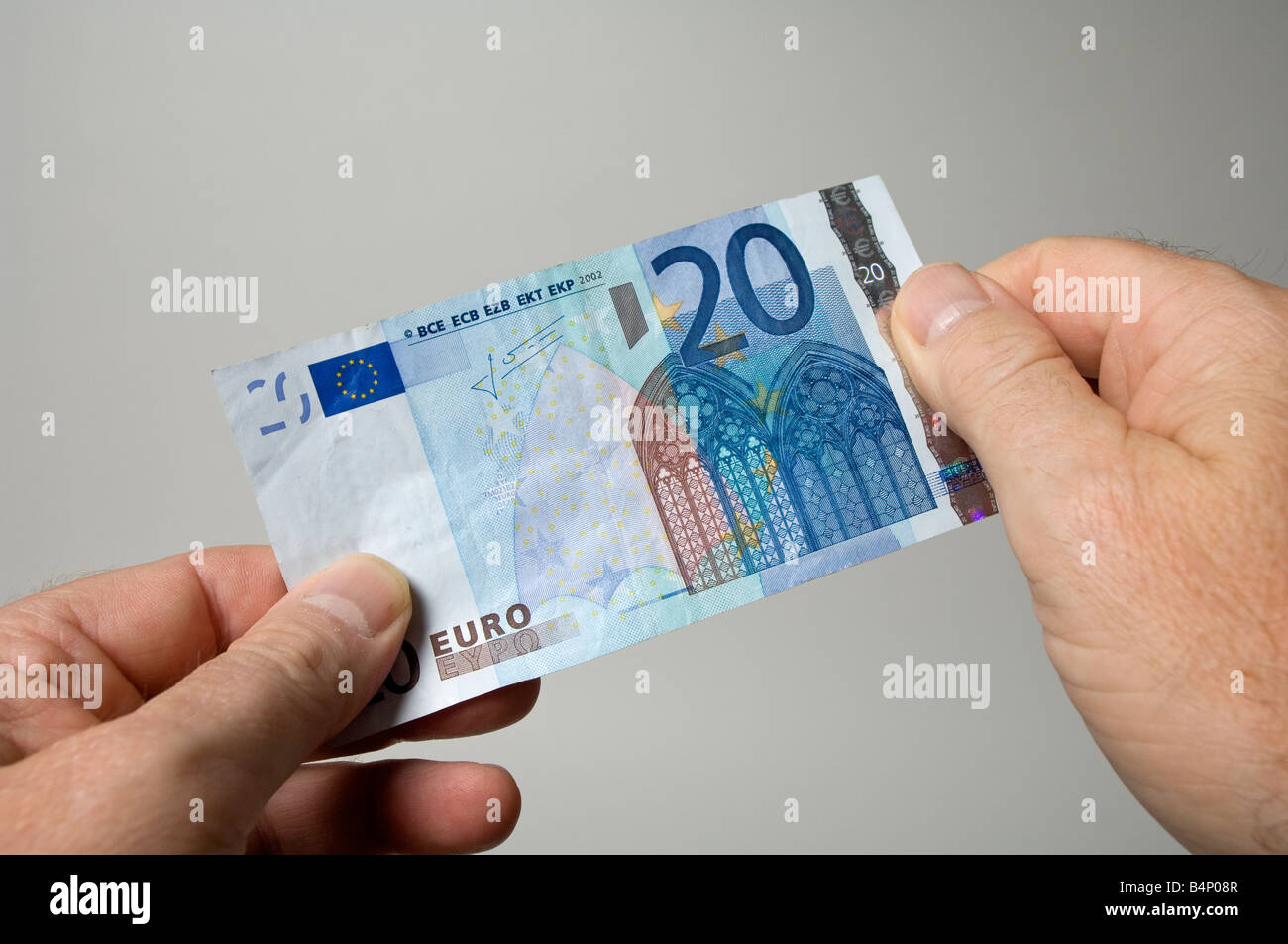 Examining a twenty euro note to check that it is genuine - Stock Image
