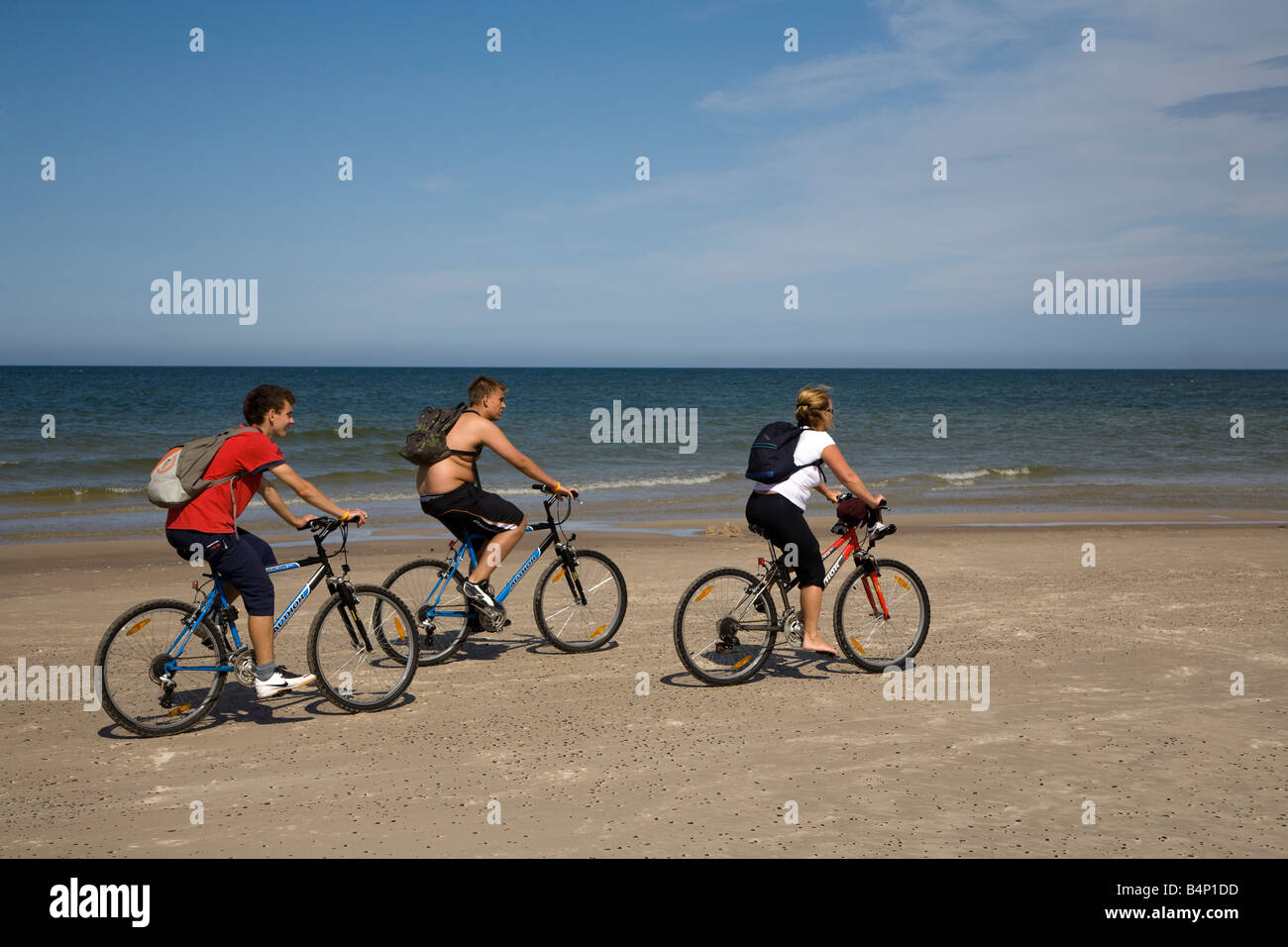 Three people cycling on beach on Baltic Sea Slowinski national park Poland - Stock Image