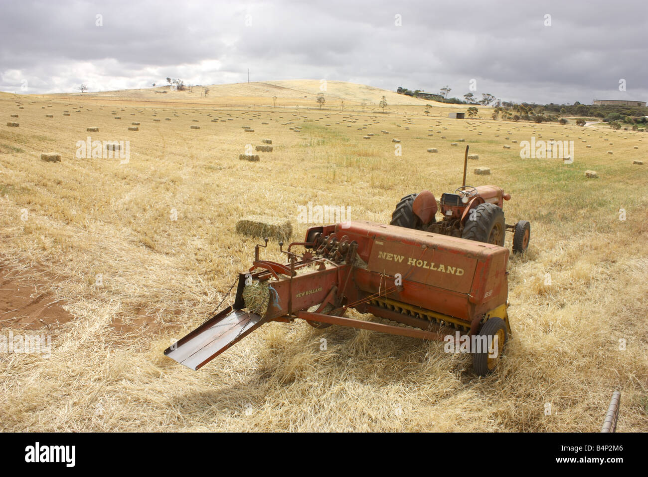 a baler and tractor on the eyre peninsula with dark clouds in background with high resolution photography - Stock Image