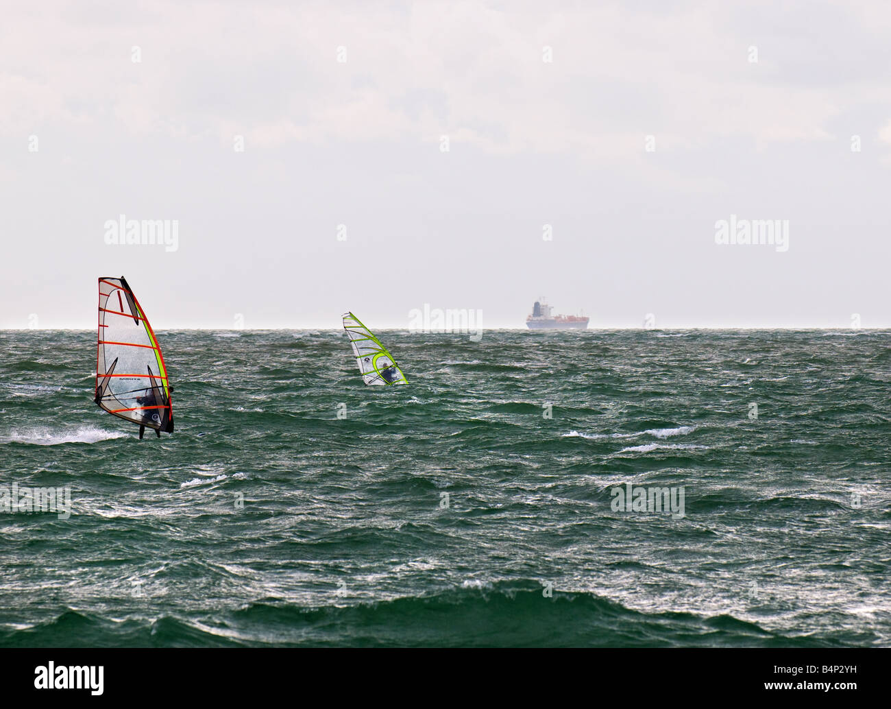 Two windsurfers in the Solent with shipping in the far distance. - Stock Image