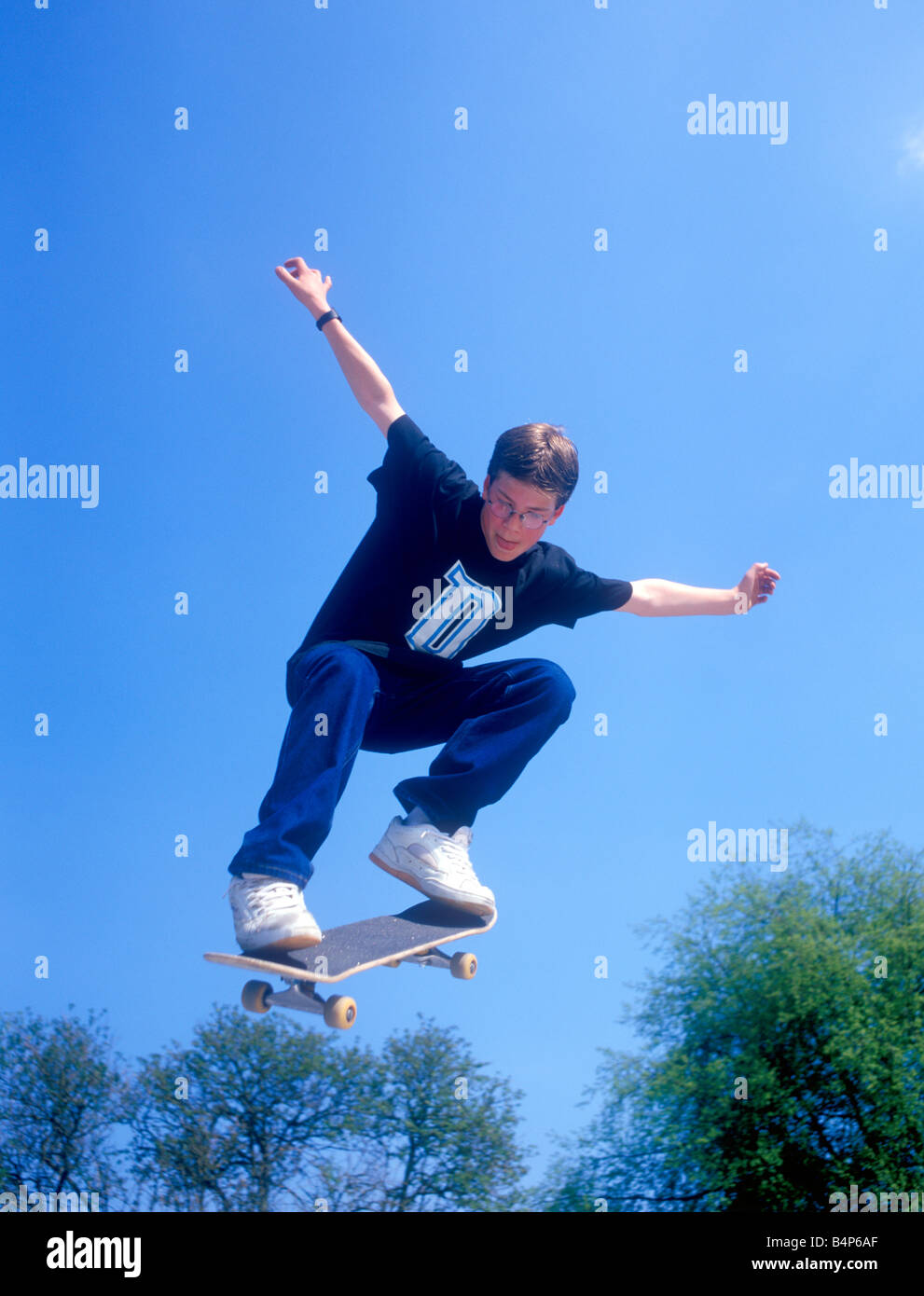 young boy jumping with his skateboard - Stock Image