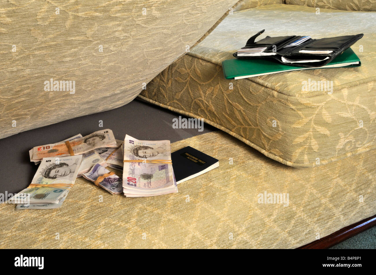 Sterling banknote money and building society pass book stored in hiding place under settee sofa chair cushion with - Stock Image