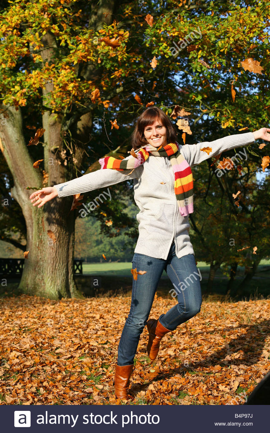 young brunette woman walking in autumn landscape throwing autumn leaves in air - Stock Image
