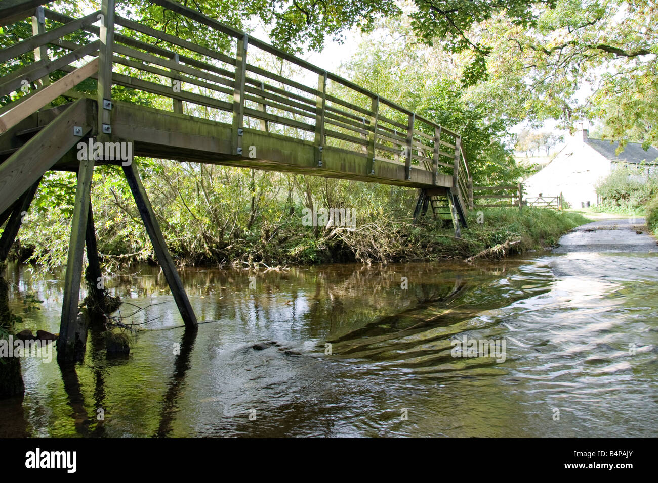 a wooden footbridge fording a little river or stream - Stock Image