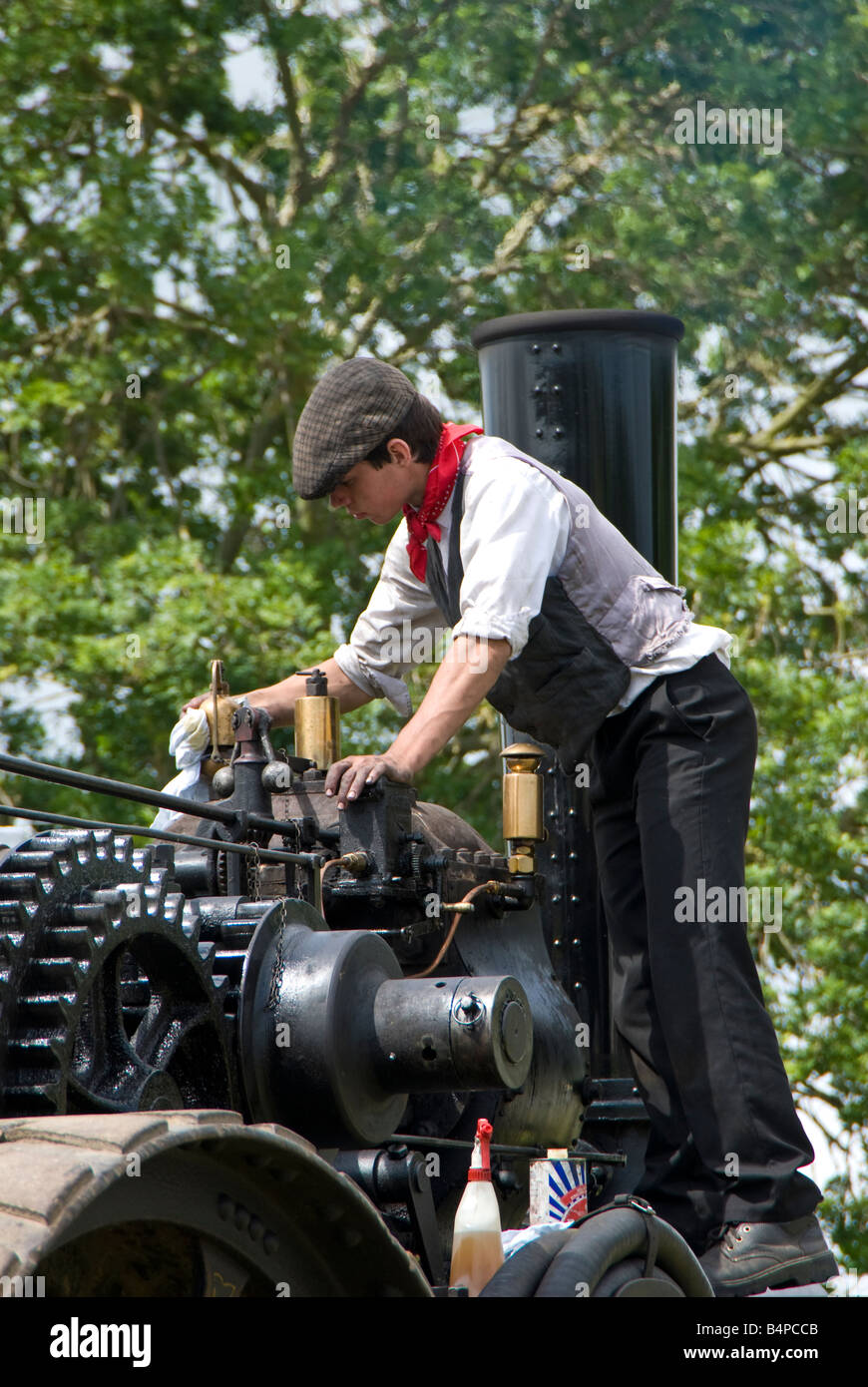 A young enthusiast cleans and maintains a steam traction engine at a vintage vehicle show. UK - Stock Image