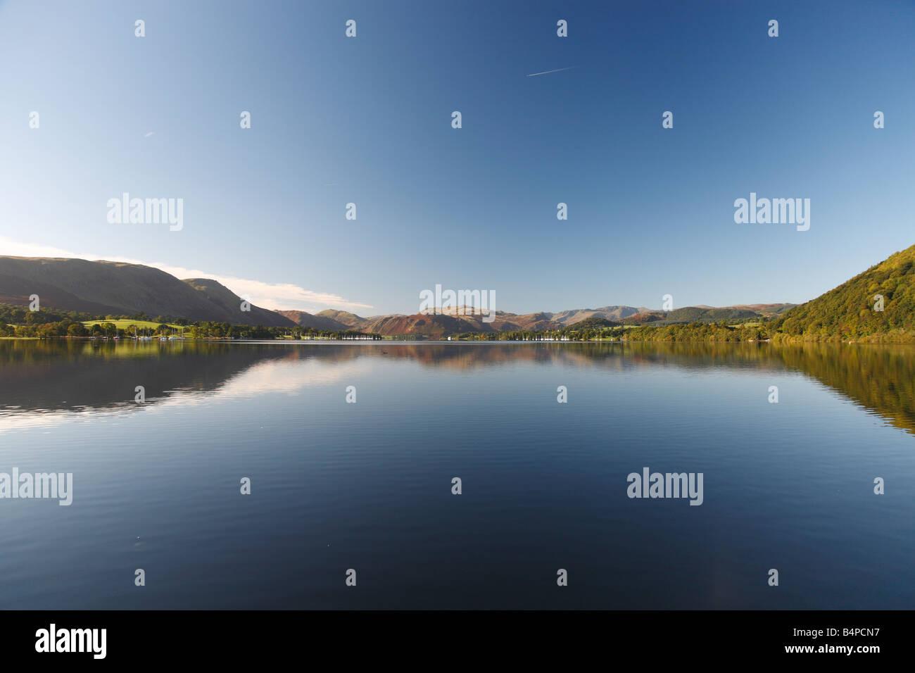 Lake scene with jetty, trees and hills. Pooley Bridge, The Lake District Cumbria, England, United Kingdom. - Stock Image
