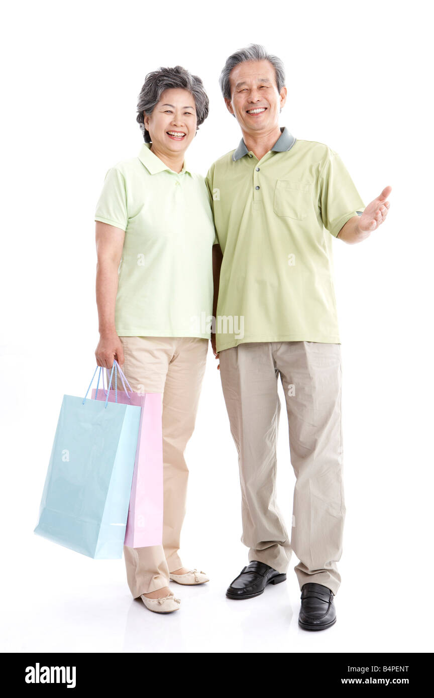 Mature couple with shopping bags, smiling - Stock Image
