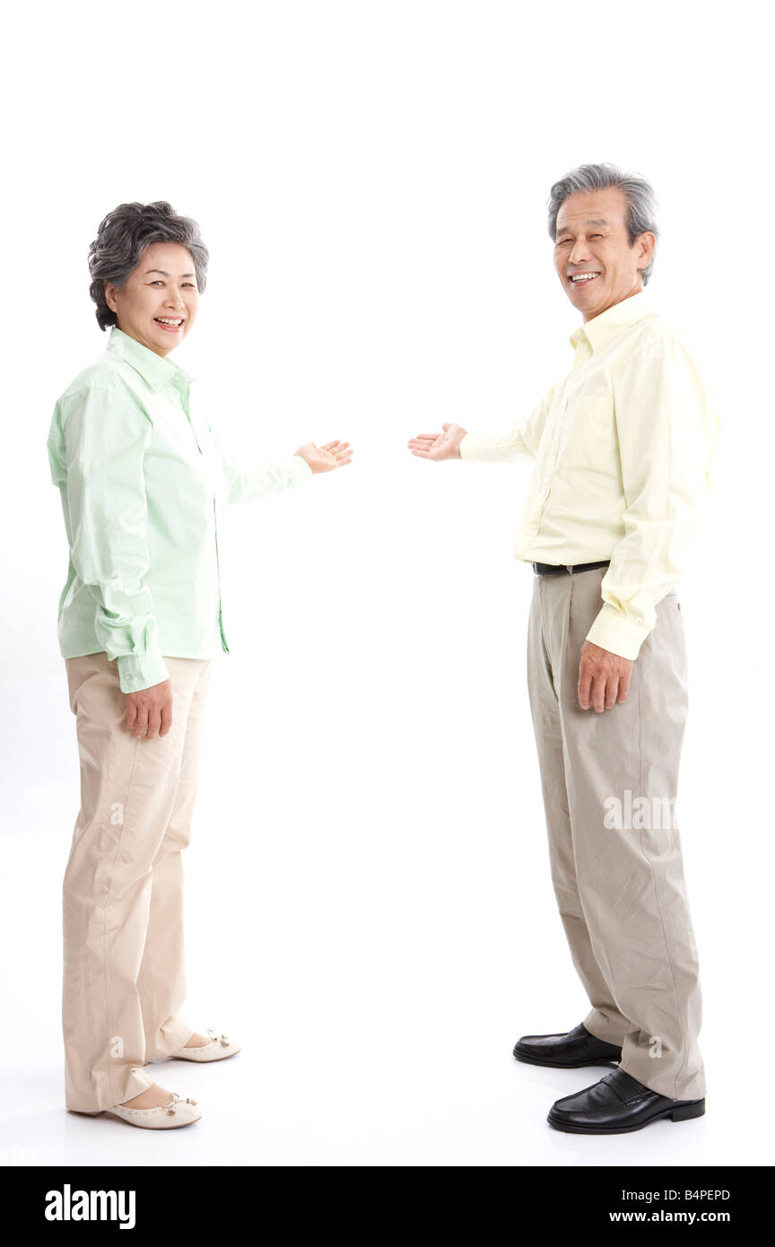 Mature couple pointing, smiling, portrait - Stock Image