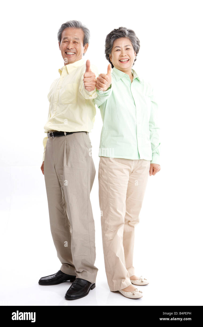 Mature couple showing thumbs up, smiling, portrait - Stock Image