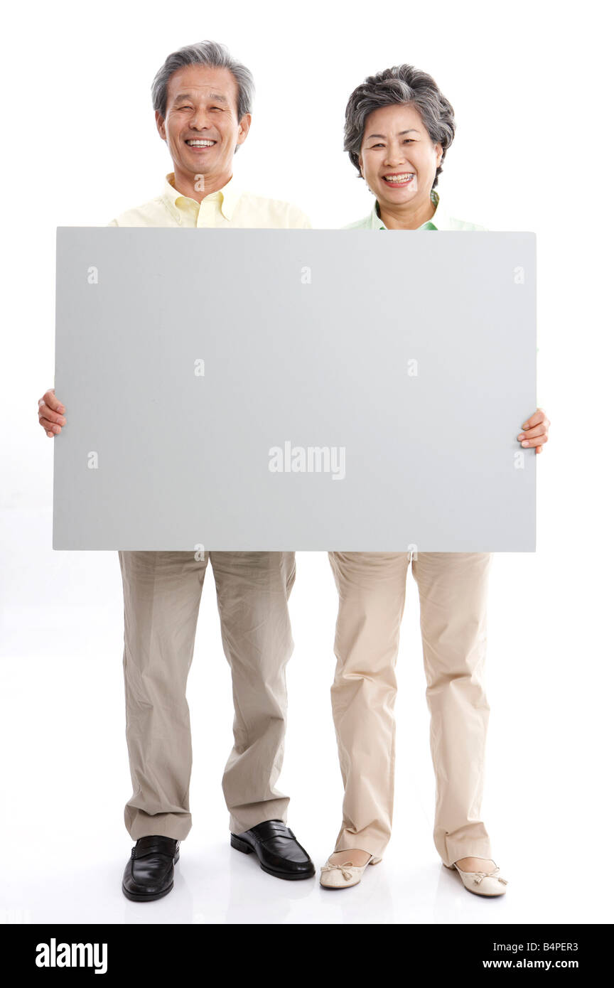 Mature couple holding blank placard, smiling, portrait - Stock Image