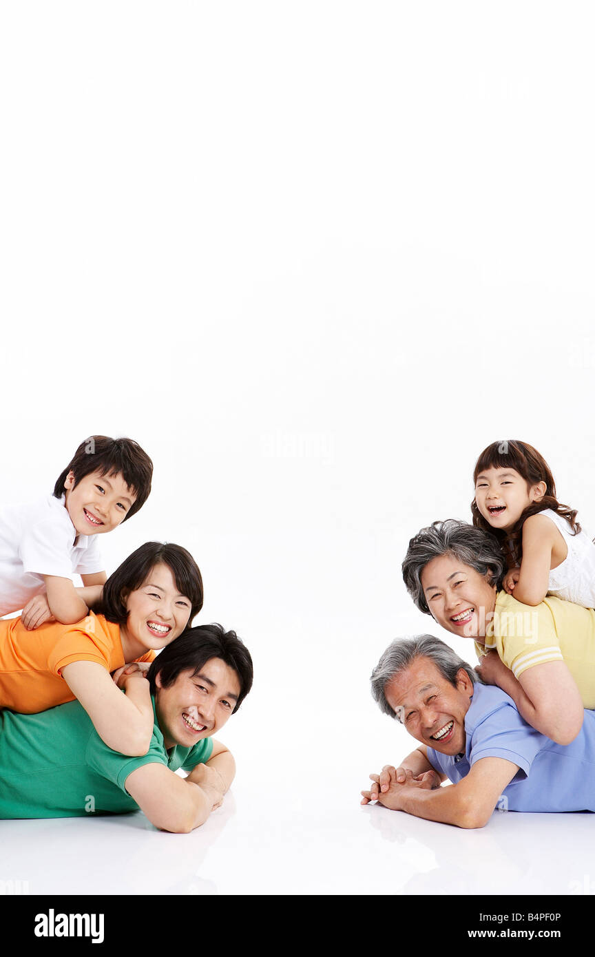Portrait of family lying on top of each other - Stock Image