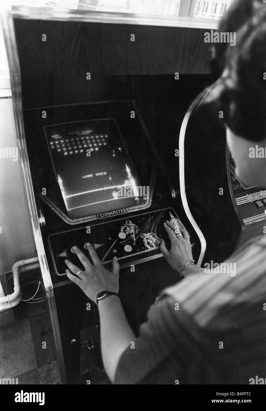 A teenager plays Space Invaders at an amusements arcade in Cardiff June 1981 - Stock Image