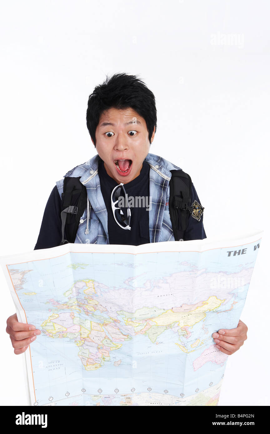 Young man looking in world map - Stock Image