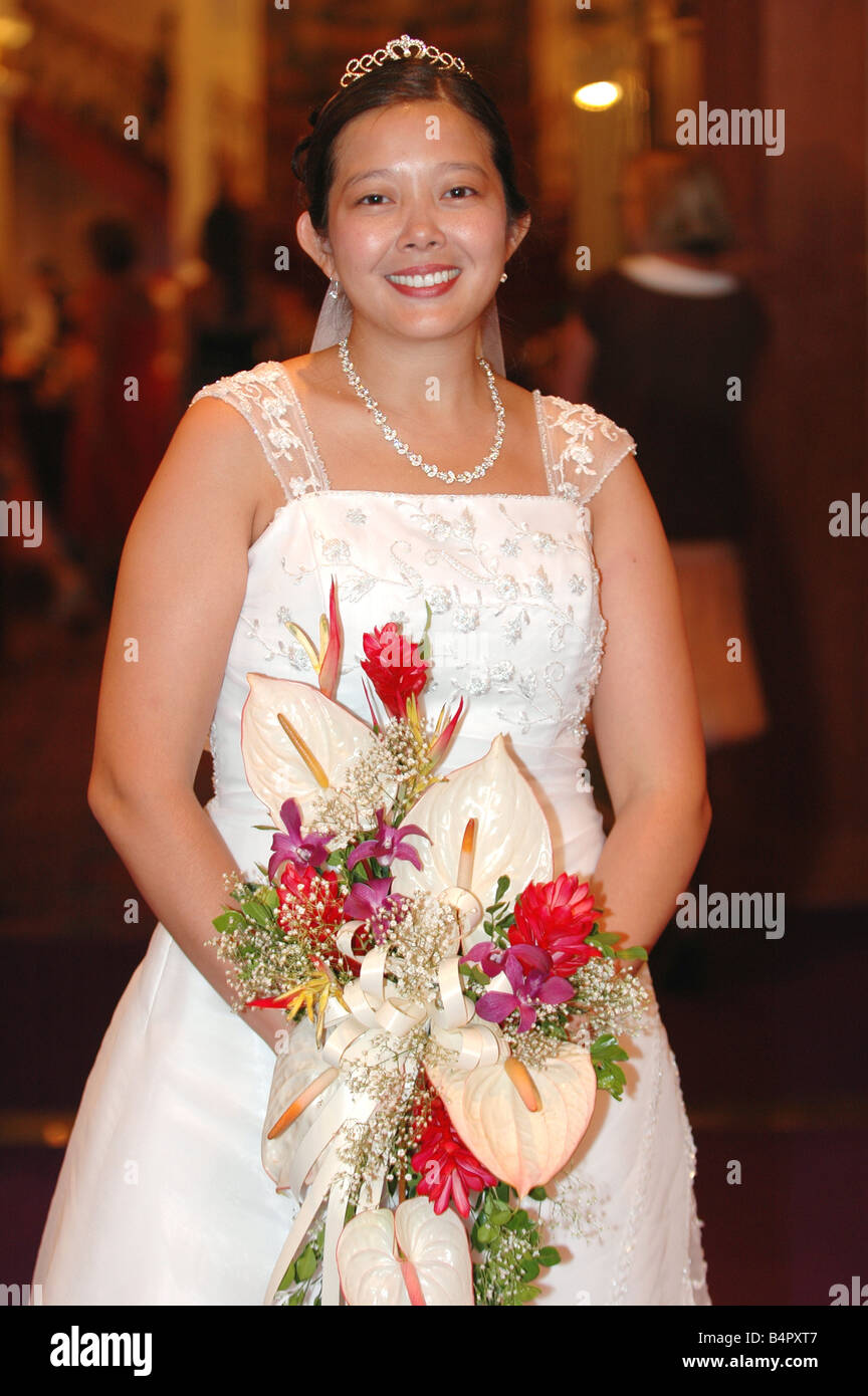 asian bride in white wedding dress holding tropical floral bouquet ...