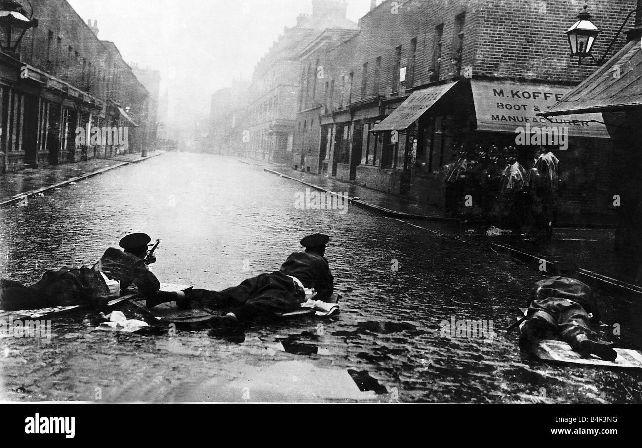 The scene from the Sidney Street Siege with Scots Guards in Rifle firing positions lying on the cobbles while Mr - Stock Image