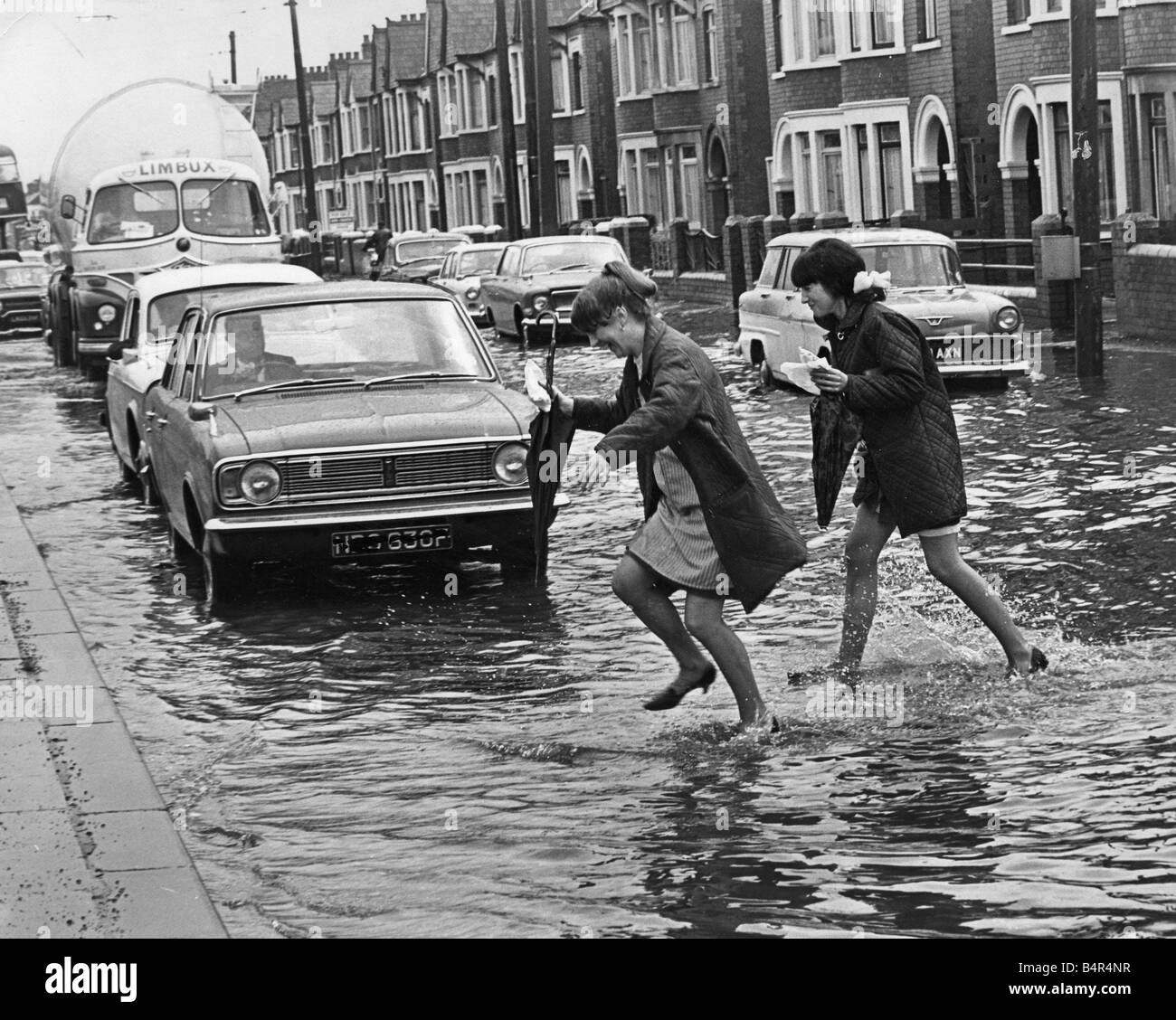 Weather Young girls Rita Thorogood and Jackie Evans dash across a flooded road during their lunch break 2nd July Stock Photo