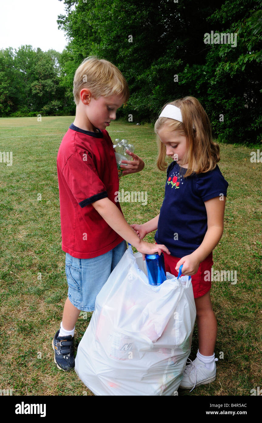 Boy and girl picking up recyclable litter in a park or field - Stock Image