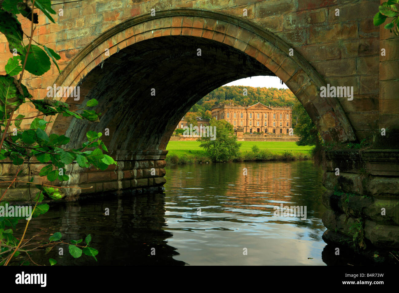 River Derwent and Chatsworth House viewed through an arch of the bridge Derbyshire England UK - Stock Image