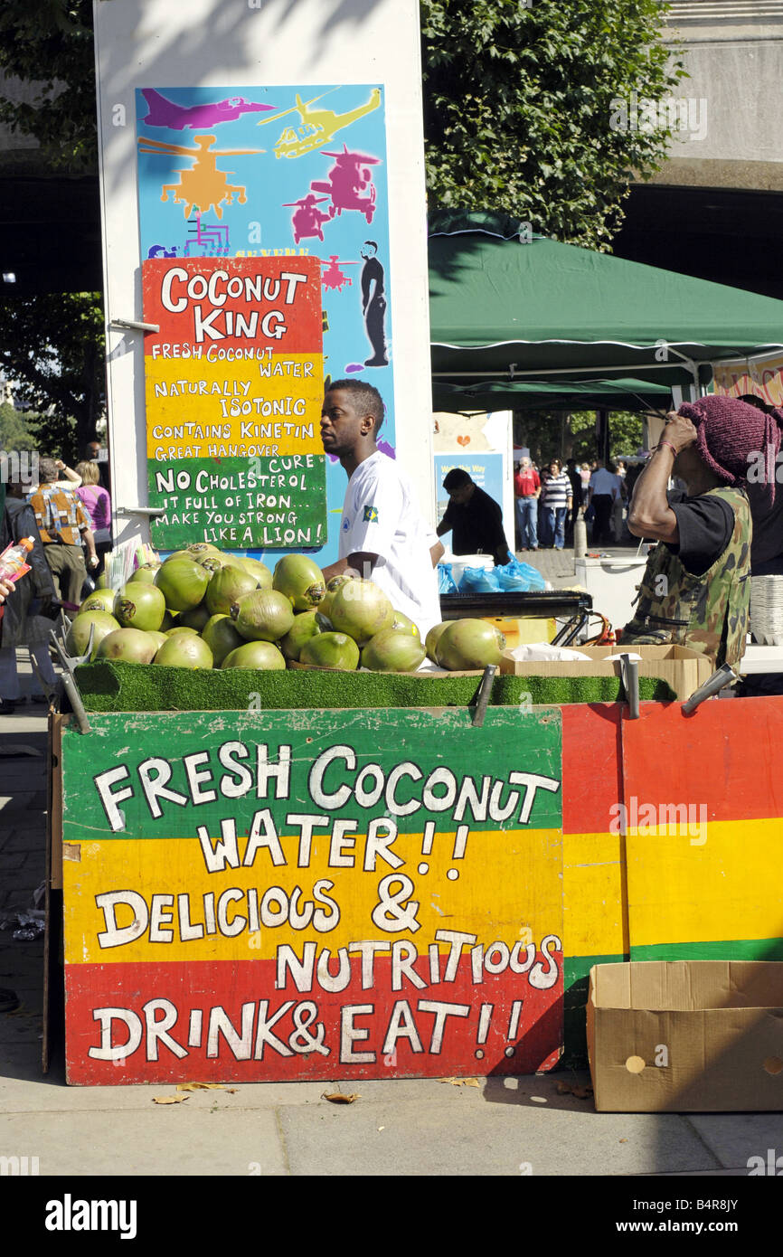 Fresh Coconut water for sale at a Carribean market stall set up in London at the thames festival - Stock Image
