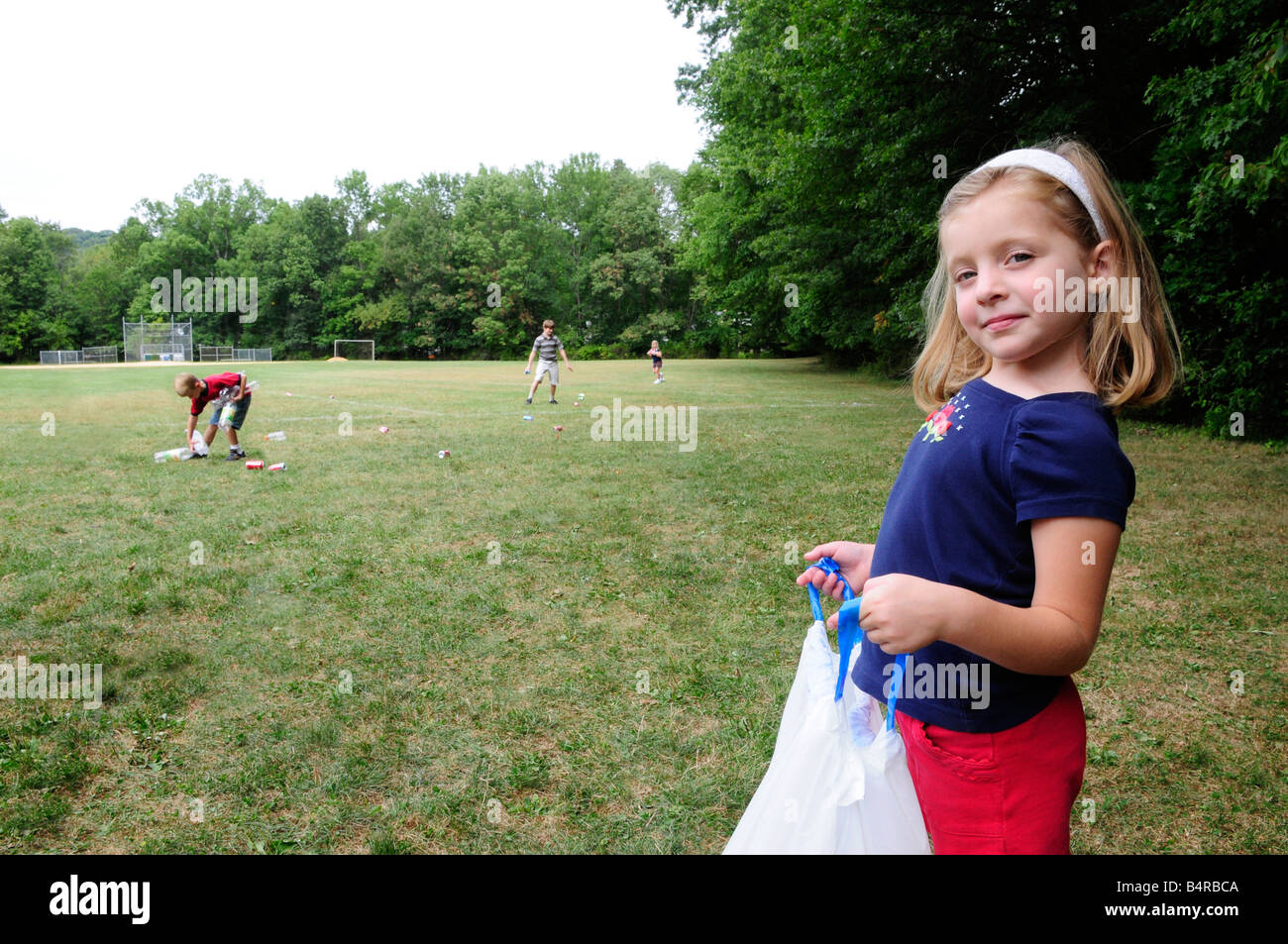 Girl holding a garbage bag helping community service effort picking up recyclable litter in a park or field - Stock Image