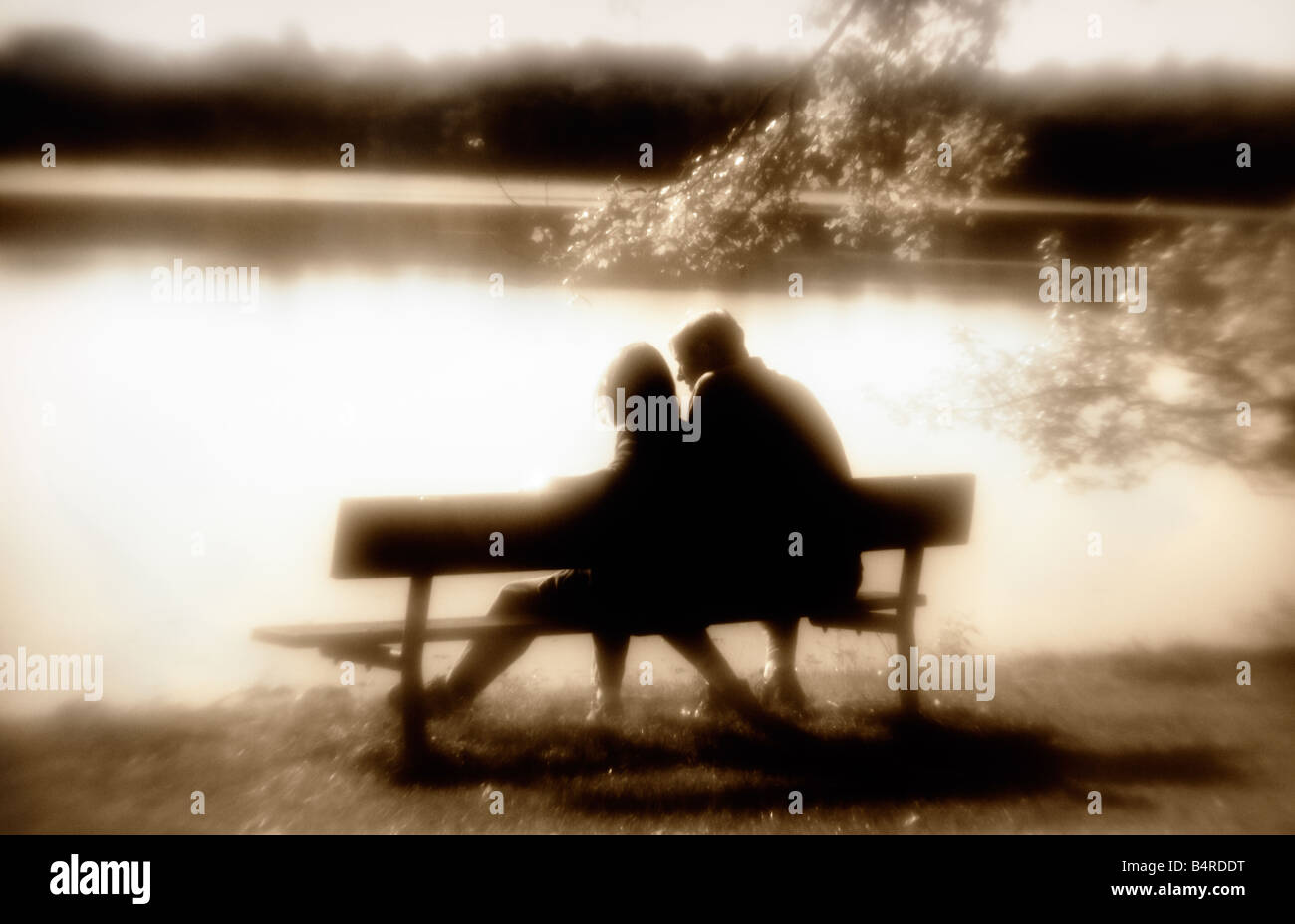 two people on a park bench silhouetted against a lake in sepia tones Stock Photo