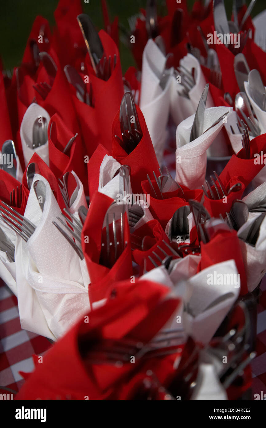knifes and forks wrapped in red and white serviettes napkins - Stock Image