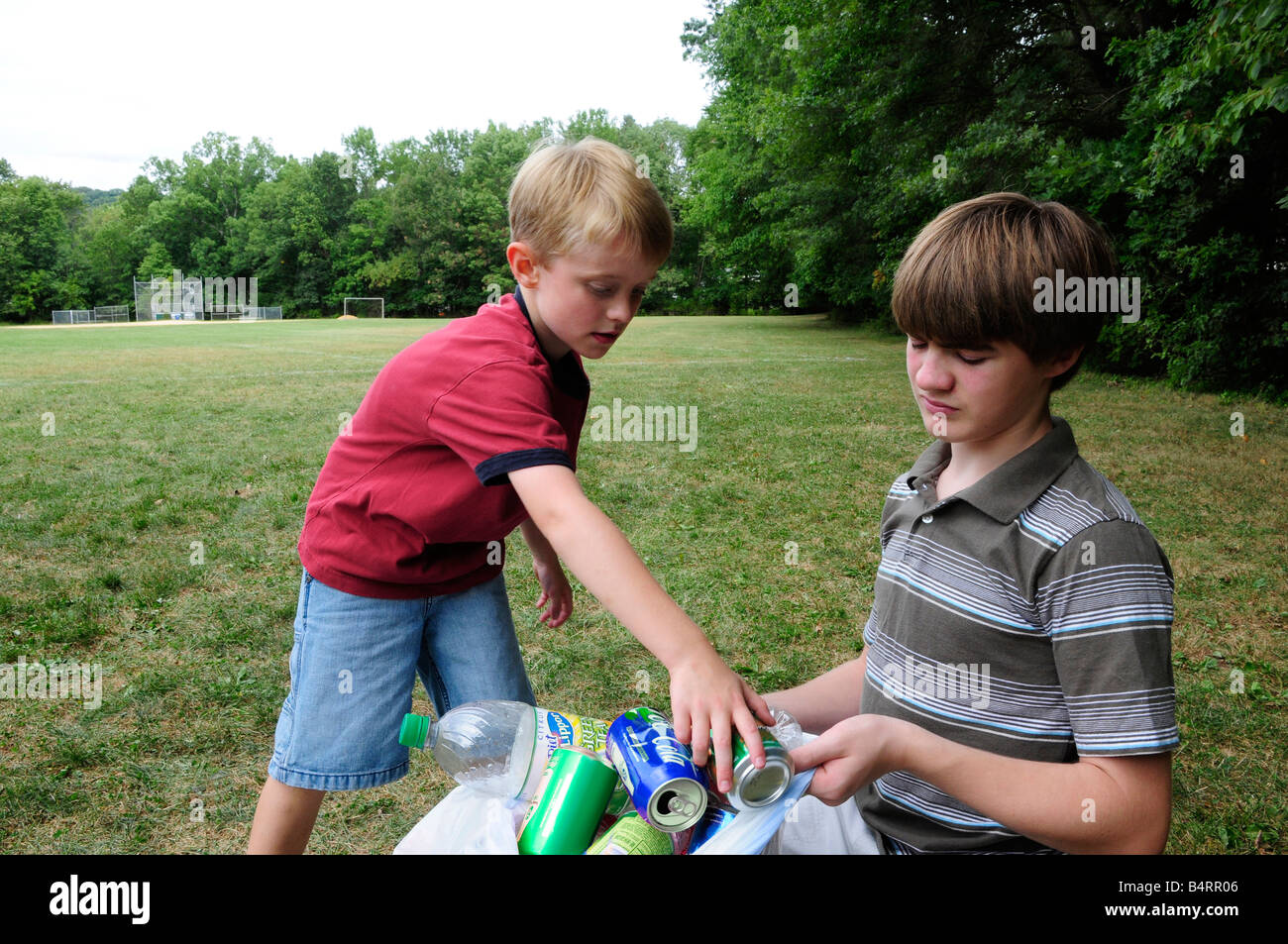 Two boys picking up recyclable litter in a field or park Stock Photo