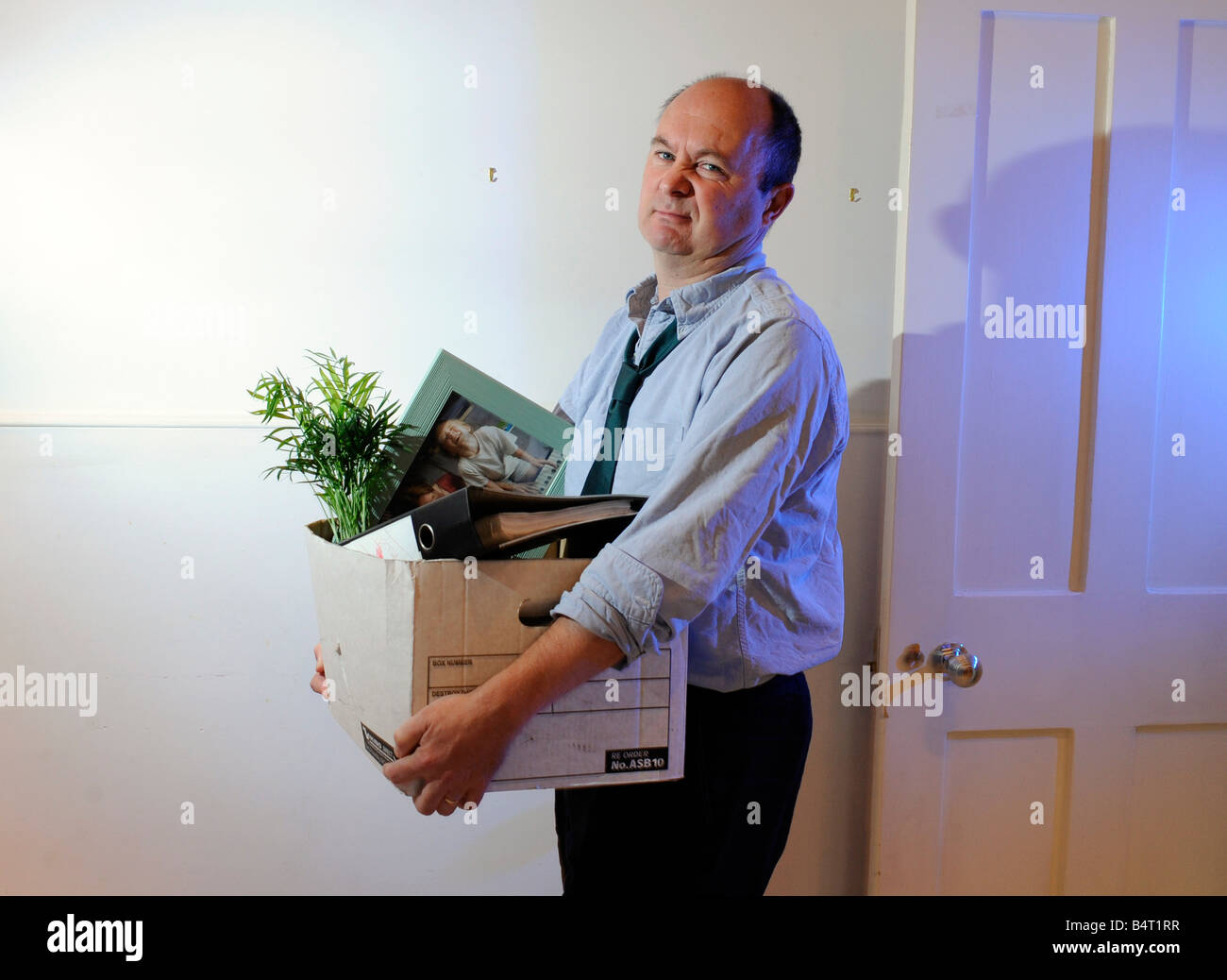 Man packs up and leaves the office after losing his job, being made redundant, being fired Stock Photo