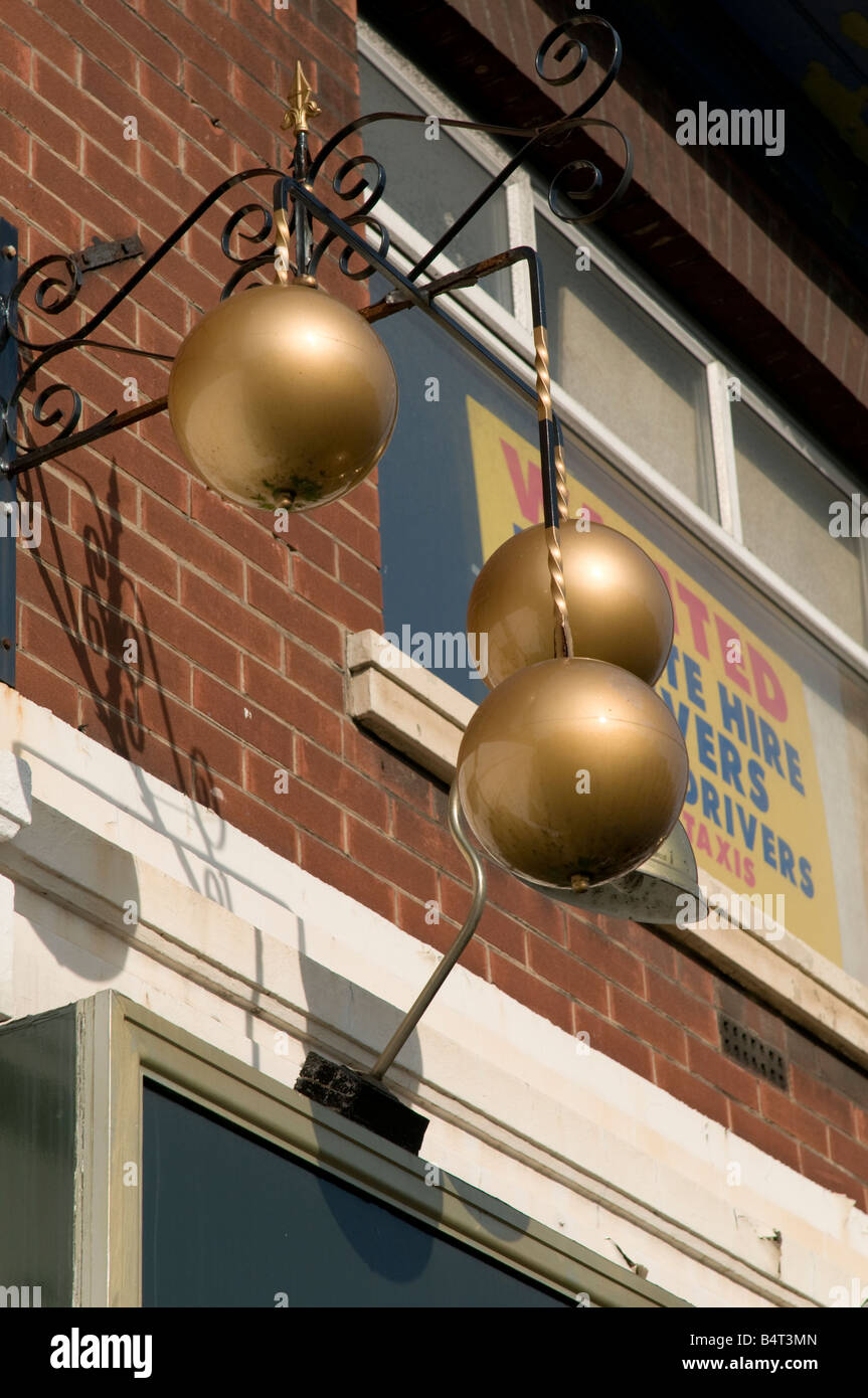 Three balls traditional pawn brokers symbol outside pawn shop Preston Lancashire England UK - Stock Image