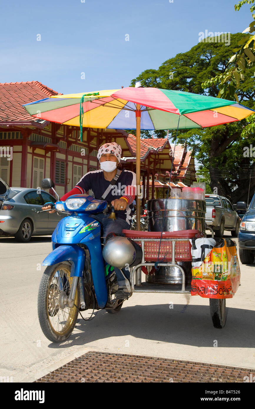 Mobile ice-cream vendor, selling ice cream, and wearing mask to provide protection against polluting vehicle emissions, - Stock Image