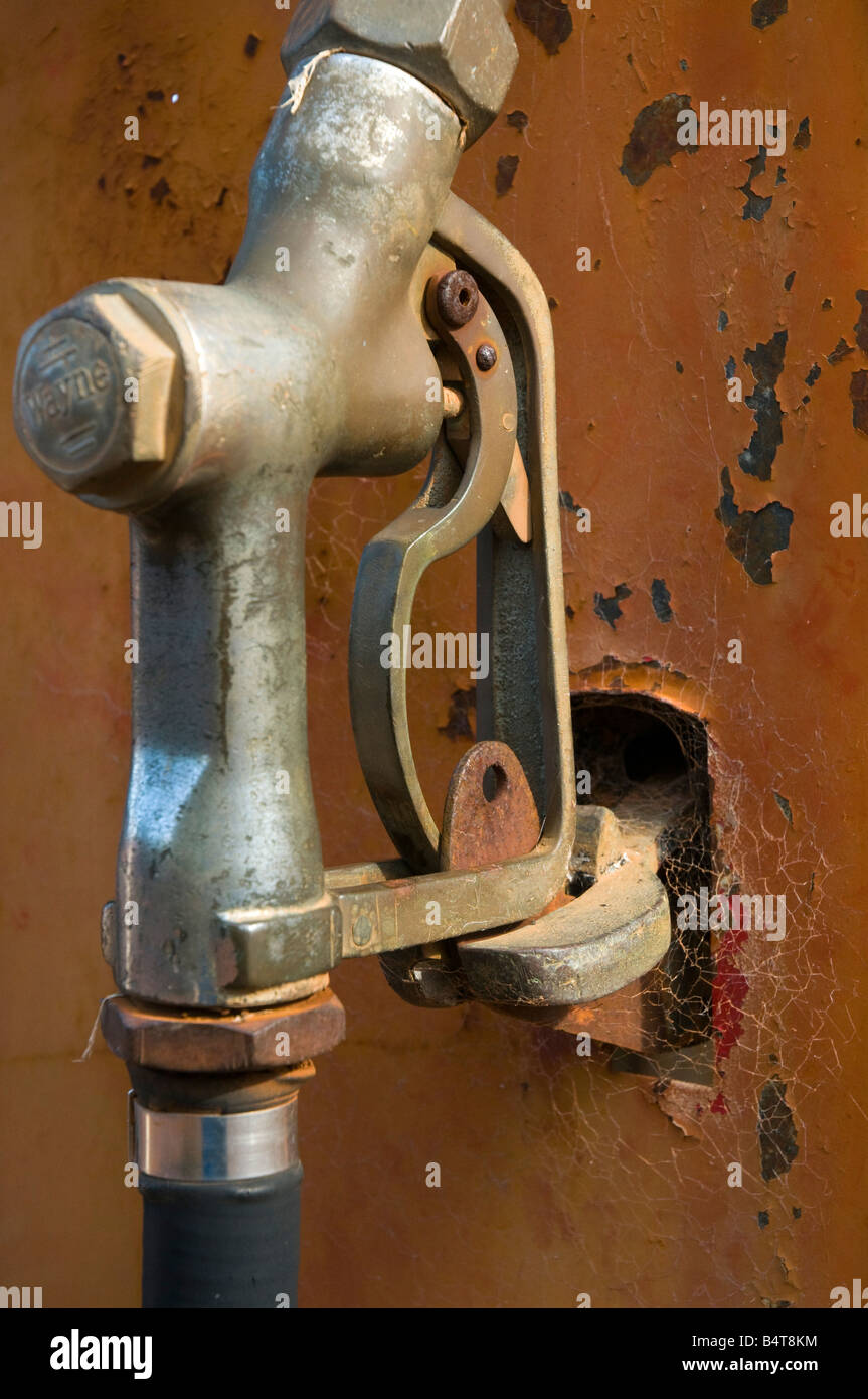 Old rusting fuel pump with spiderwebs growing on the nozzle - Stock Image