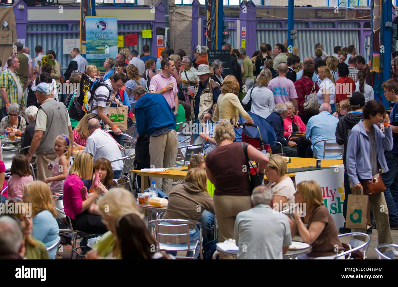 Crowds of people wander sit and browse stalls ain Market Hall at Abergavenny Food Festival Stock Photo