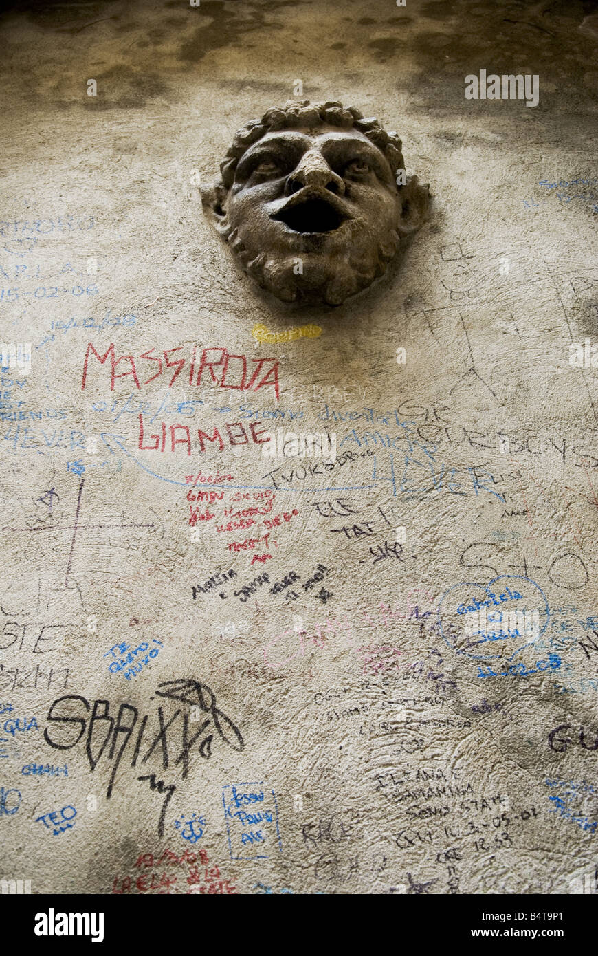 looking up at a medieval relief face with open mouth on wall covered with multicoloured graffiti in central bergamo, - Stock Image