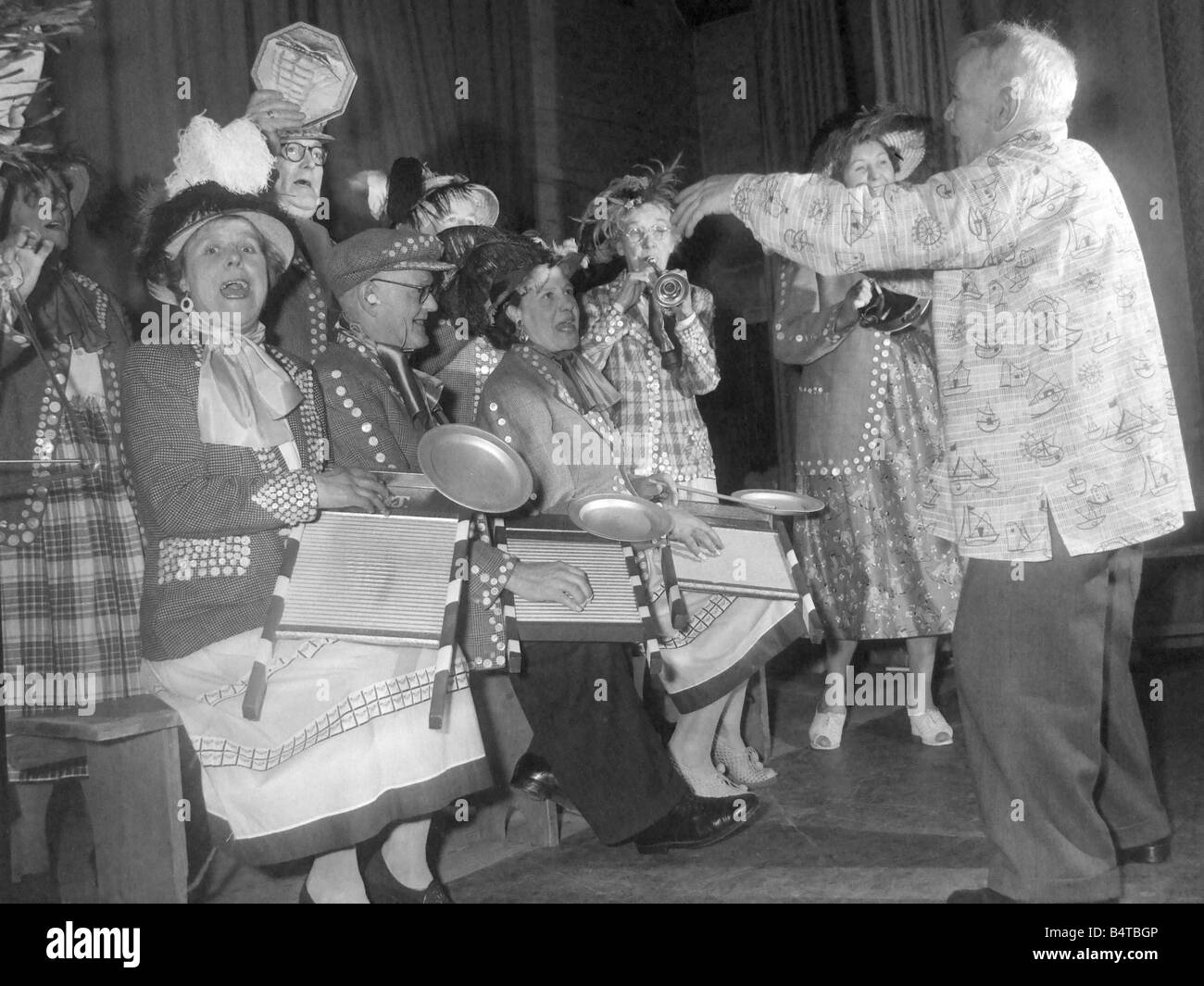 Pearly kings and queens play the washboard and other musical instruments during a concert - Stock Image