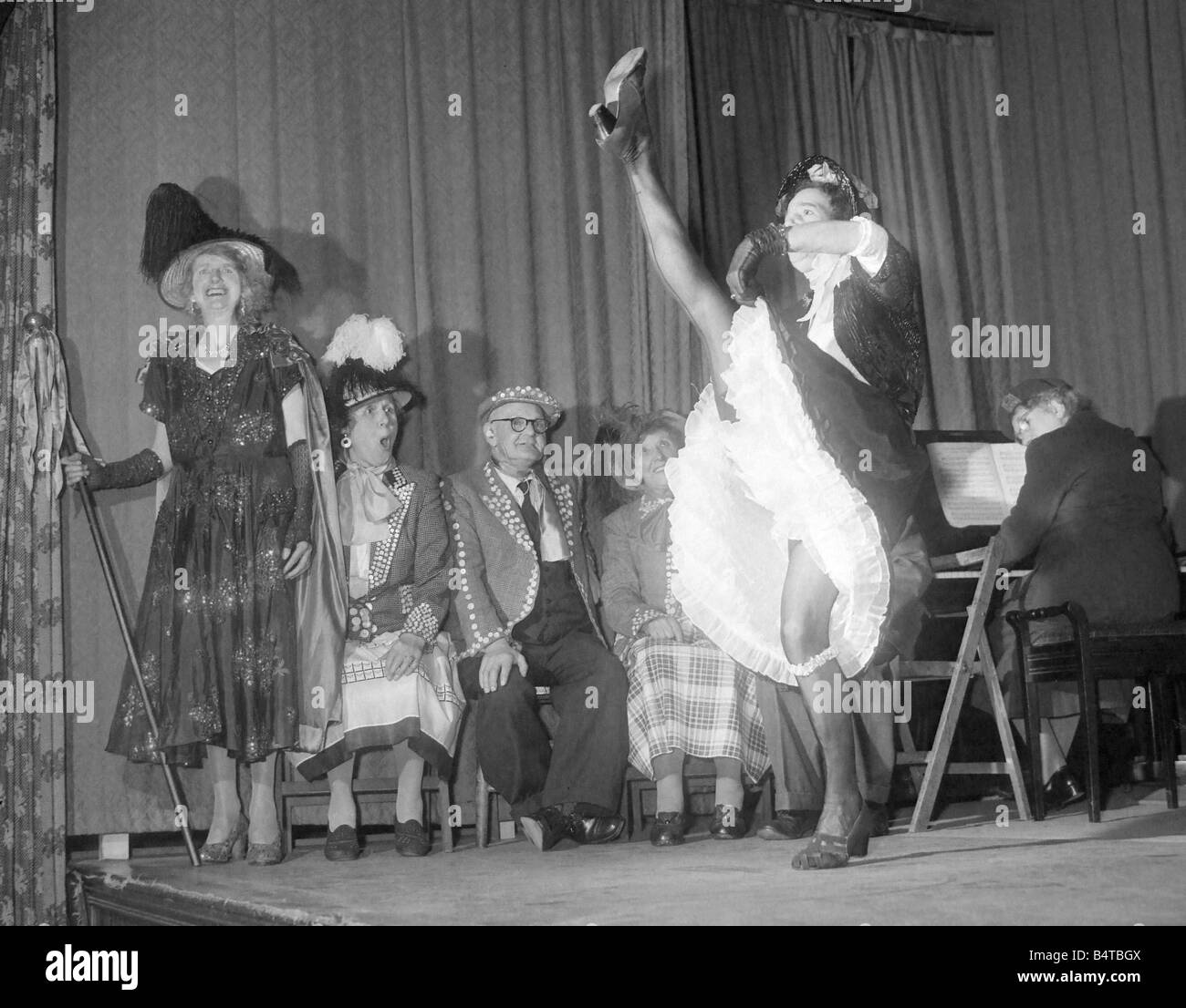 Old lady performs the can can during a concert by pearly kings and queens - Stock Image