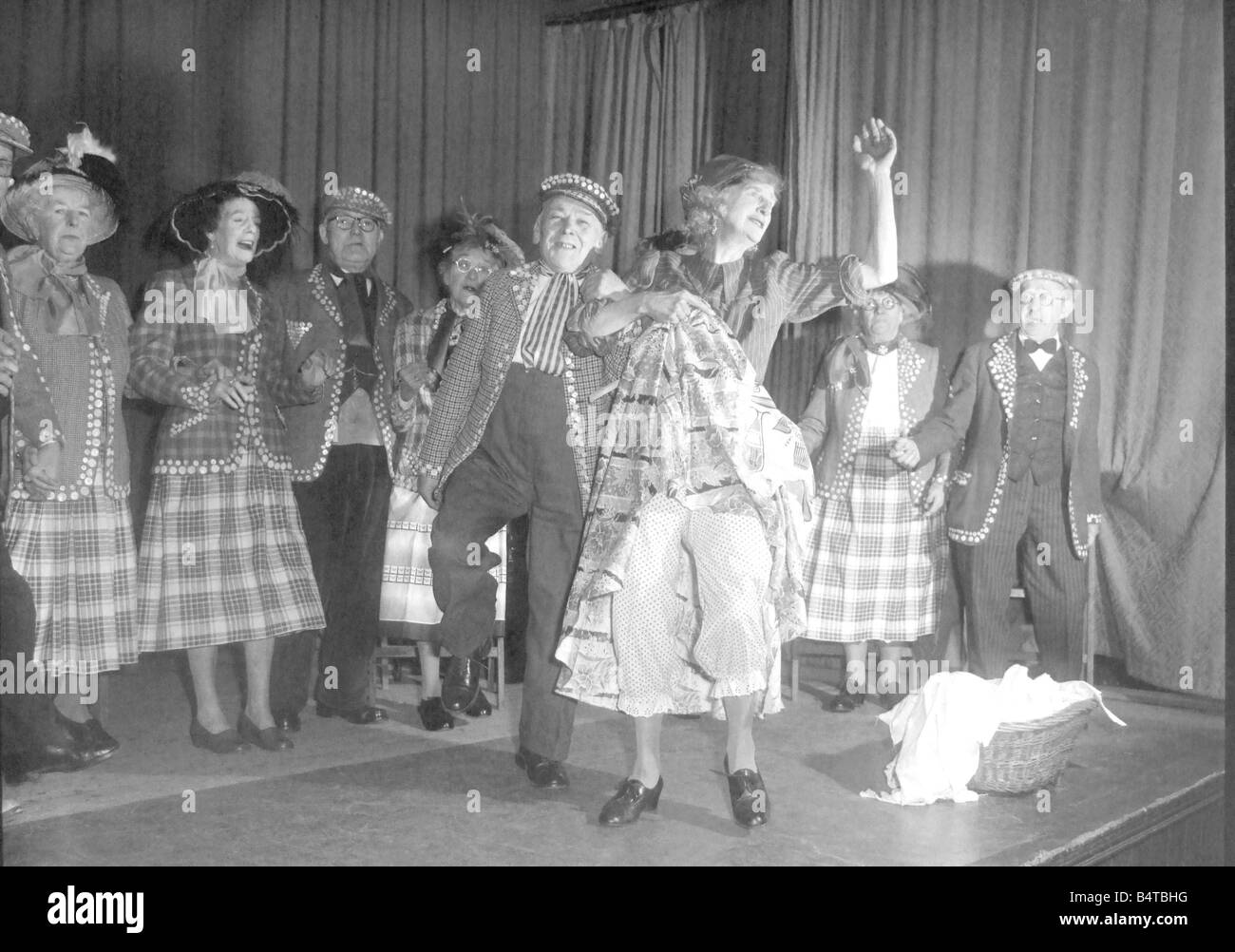 Old people dressed as Pearly Kings and Queens dancing on stage during a concert Woman showing her bloomers - Stock Image