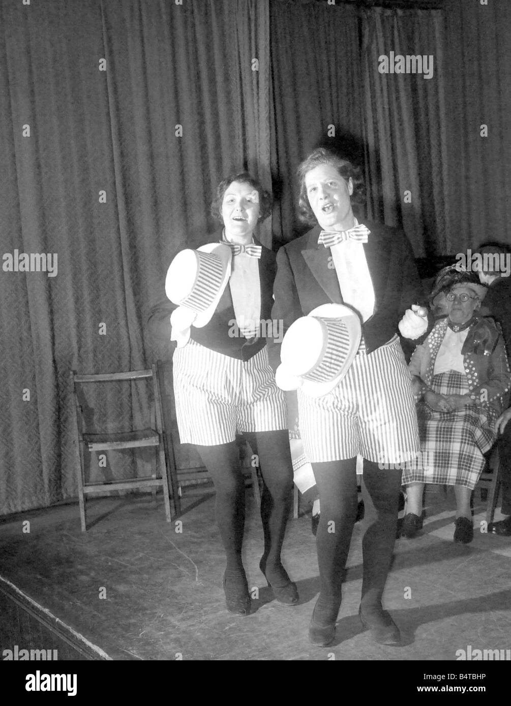 Two ladies performing on stage during a pearly kings and queens concert party - Stock Image