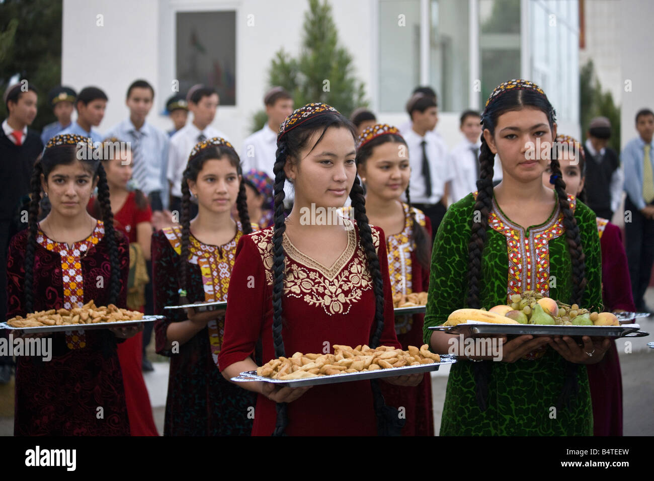 Turkmen girls offering food for delegates at a dance performance beside the road on the outskirts of Ashgabat - Stock Image