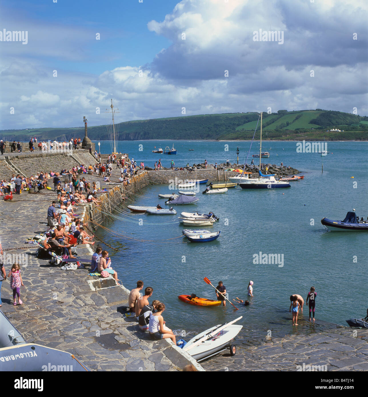 People sitting on the stone quay at New Quay Ceredigion Wales UK - Stock Image