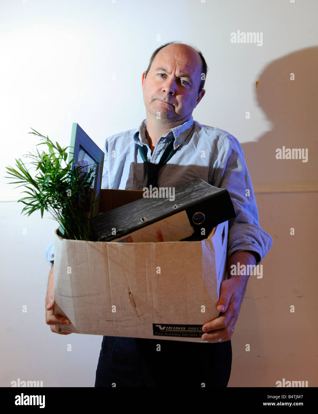 Man packs up and leaves the office after losing his job, being made redundant, being fired - Stock Image