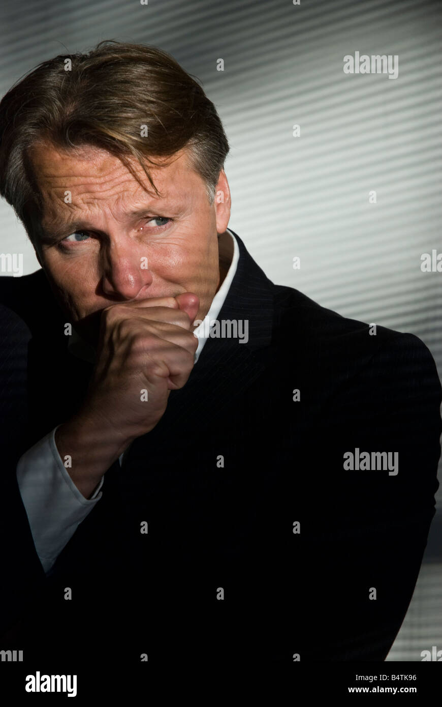 A depressed and desperate looking businessman holds back the tears after going bankrupt. - Stock Image