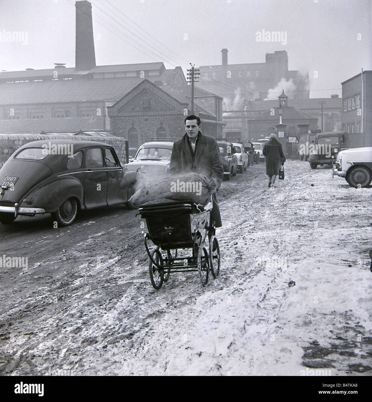 A gentleman wheels his sack of coal back from the coal merchant January 1963 The winter of 1963 was one of the worst - Stock Image